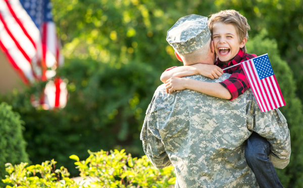 Man in Army uniform hugs small boy holding American Flag.